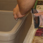 Artist smooths the fireclay sink